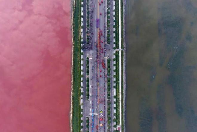 Çin  Su yosunlarından ötürü nehri iki farklı renge bölen köprü.